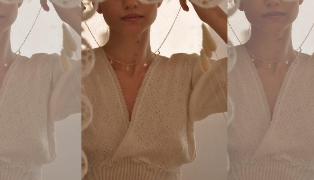 鏡を見てアクセサリーを付ける女性